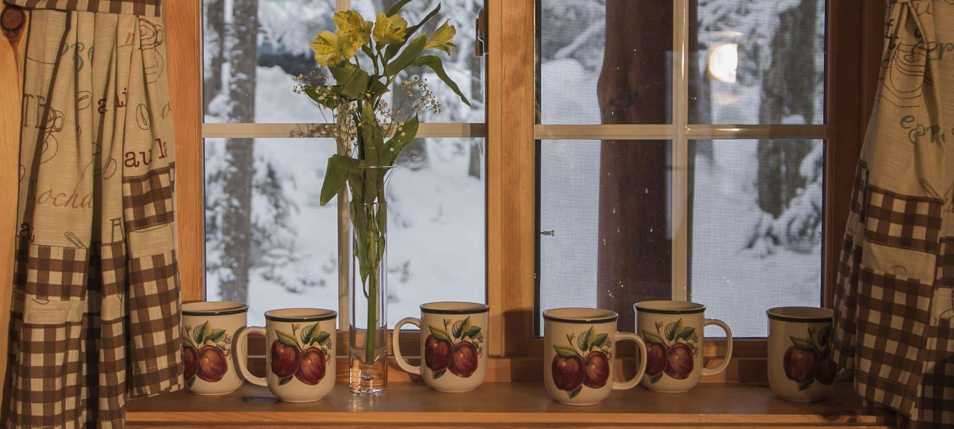 Window with checkered curtains, ceramic mugs with painted apples on the sill and a tall slender glass vase with yellow flowers