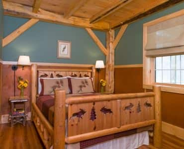 Cabin guest room, rustic wooden carved bed, two nightstands with lamps, blue-green walls, wood floors and window with shade