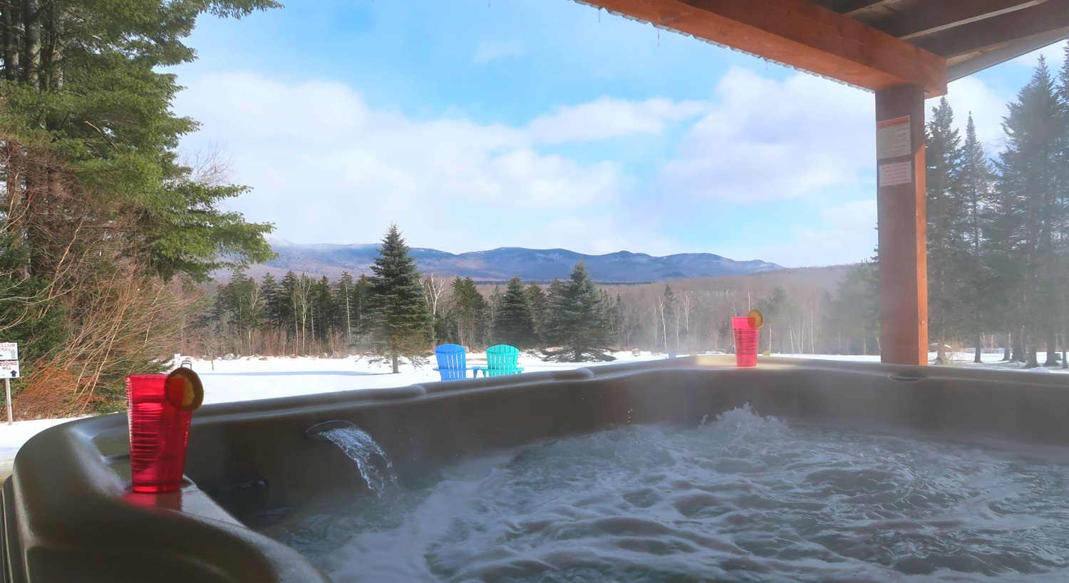 View from bubbling hot tub of snow-covered ground and trees and hills in the background