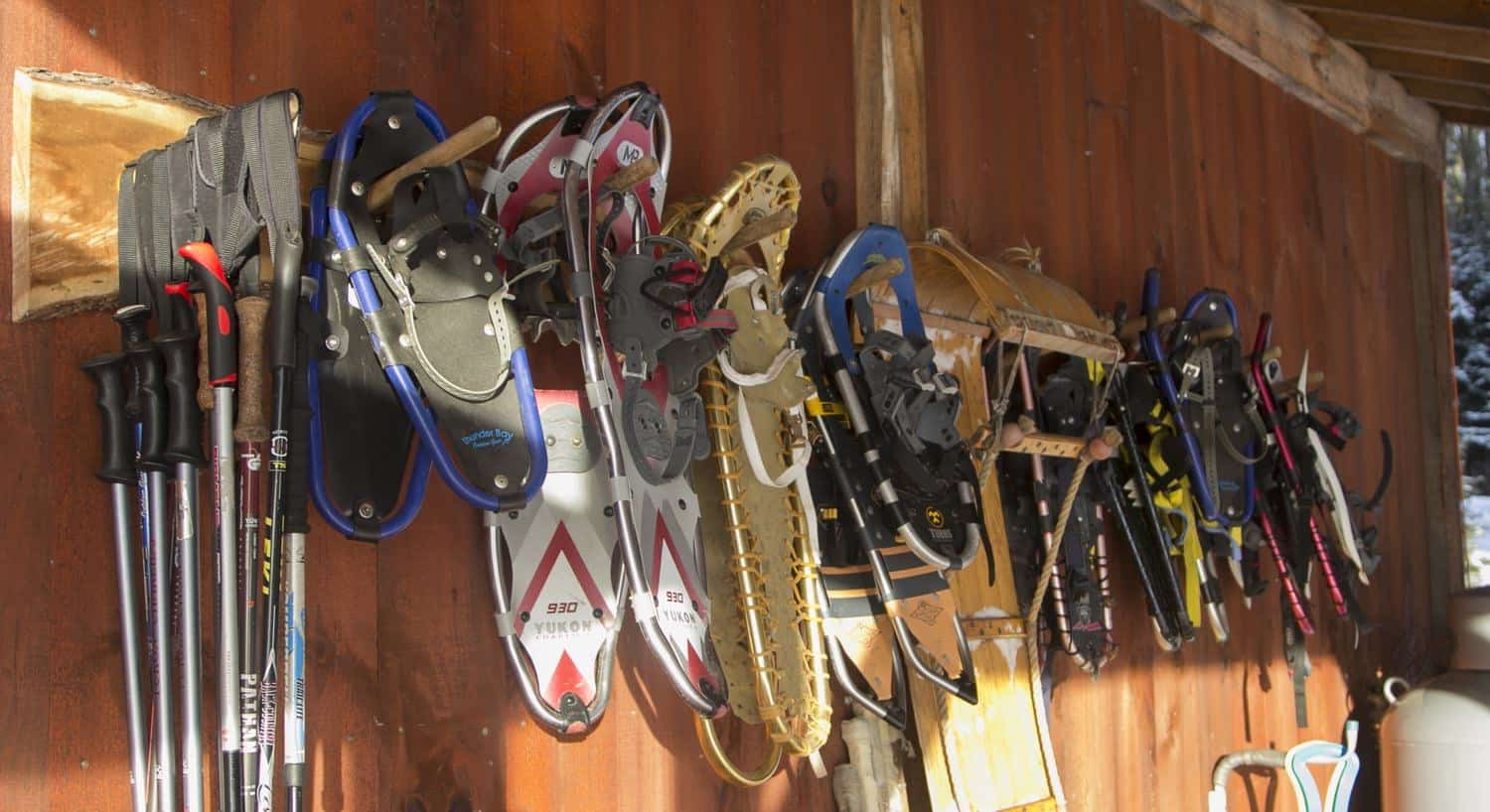 Assorted snowshoes and skis hanging from a  wood cabin wall