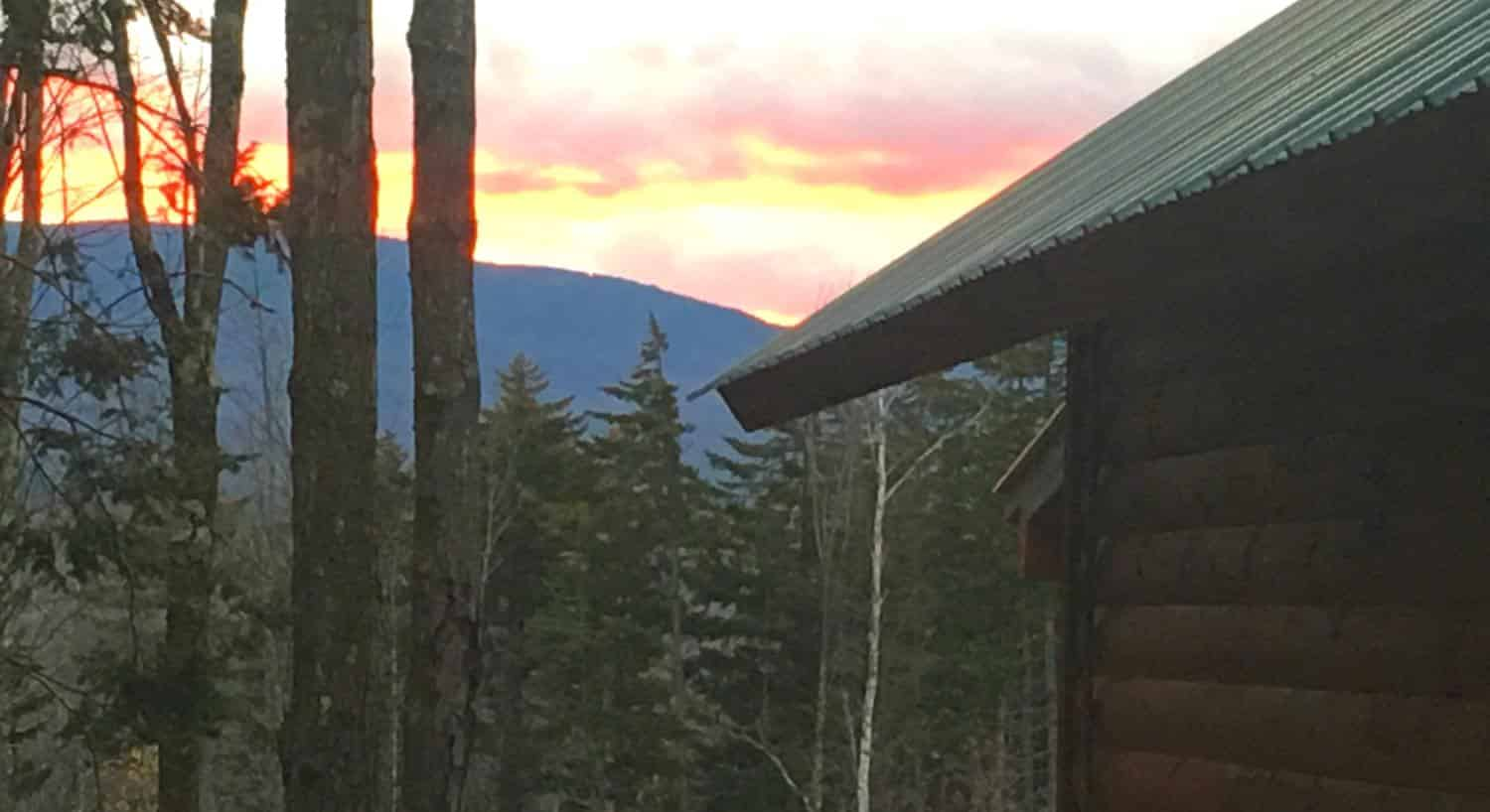 View from the side of a cabin of the sunset sky over distant hills and pine trees