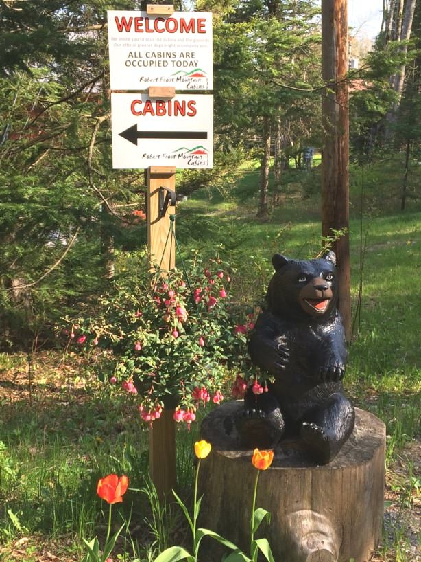Painted carved bear on a tree stump surrounded by flowers and a directional sign to the cabins