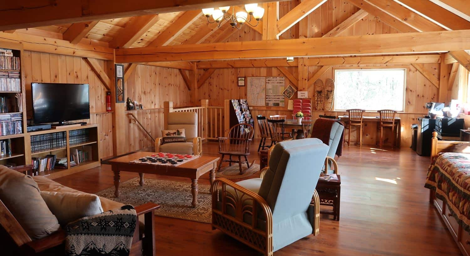 Inside the wooden community cabin with furniture, TV, books, games, dining tables and chairs and bar seating under the window
