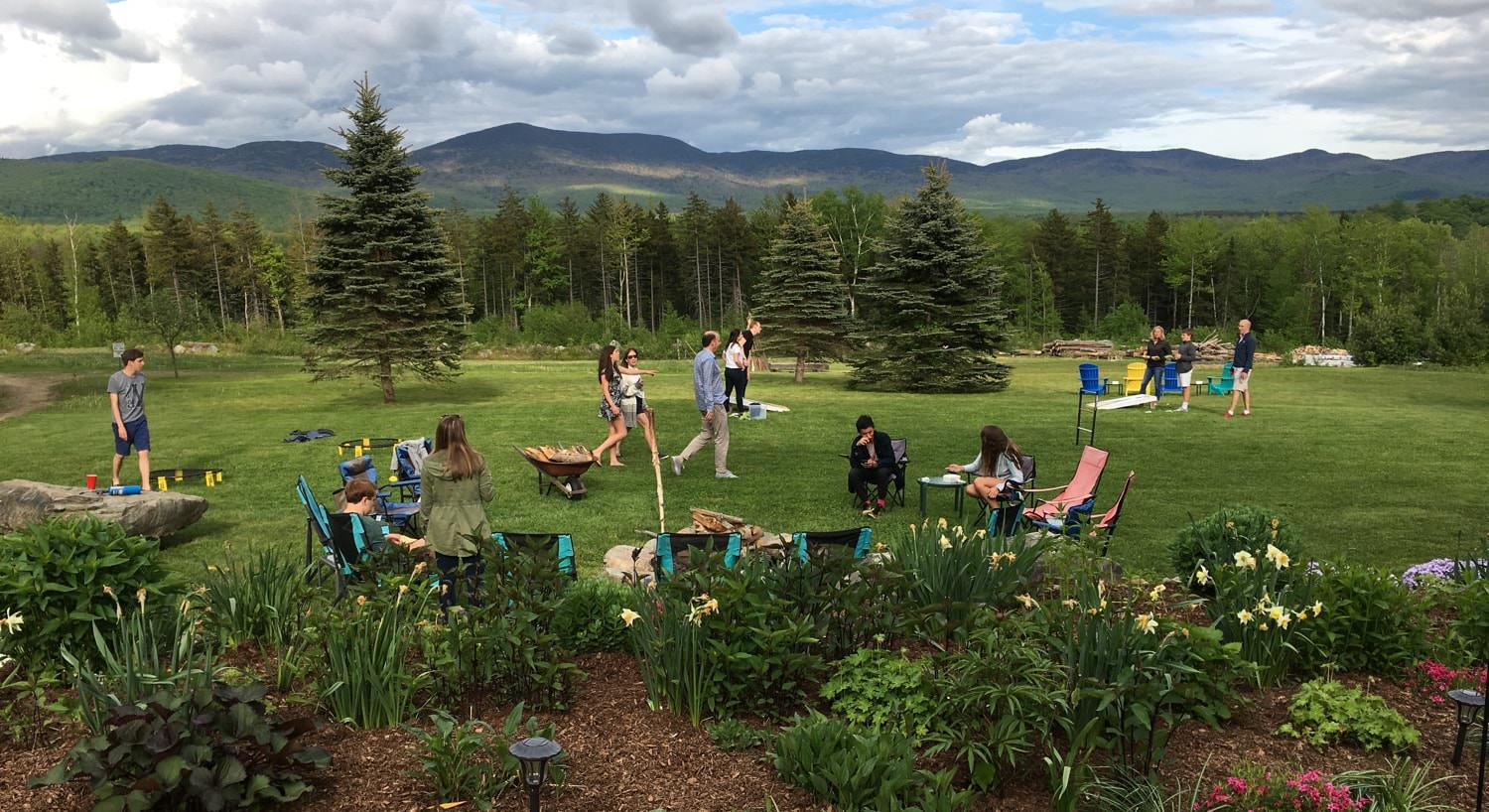 Several people in the common area enjoying yard games and the campfire surrounded by pine trees and distant hills