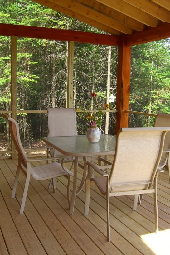 Covered screened-in deck with table and chairs