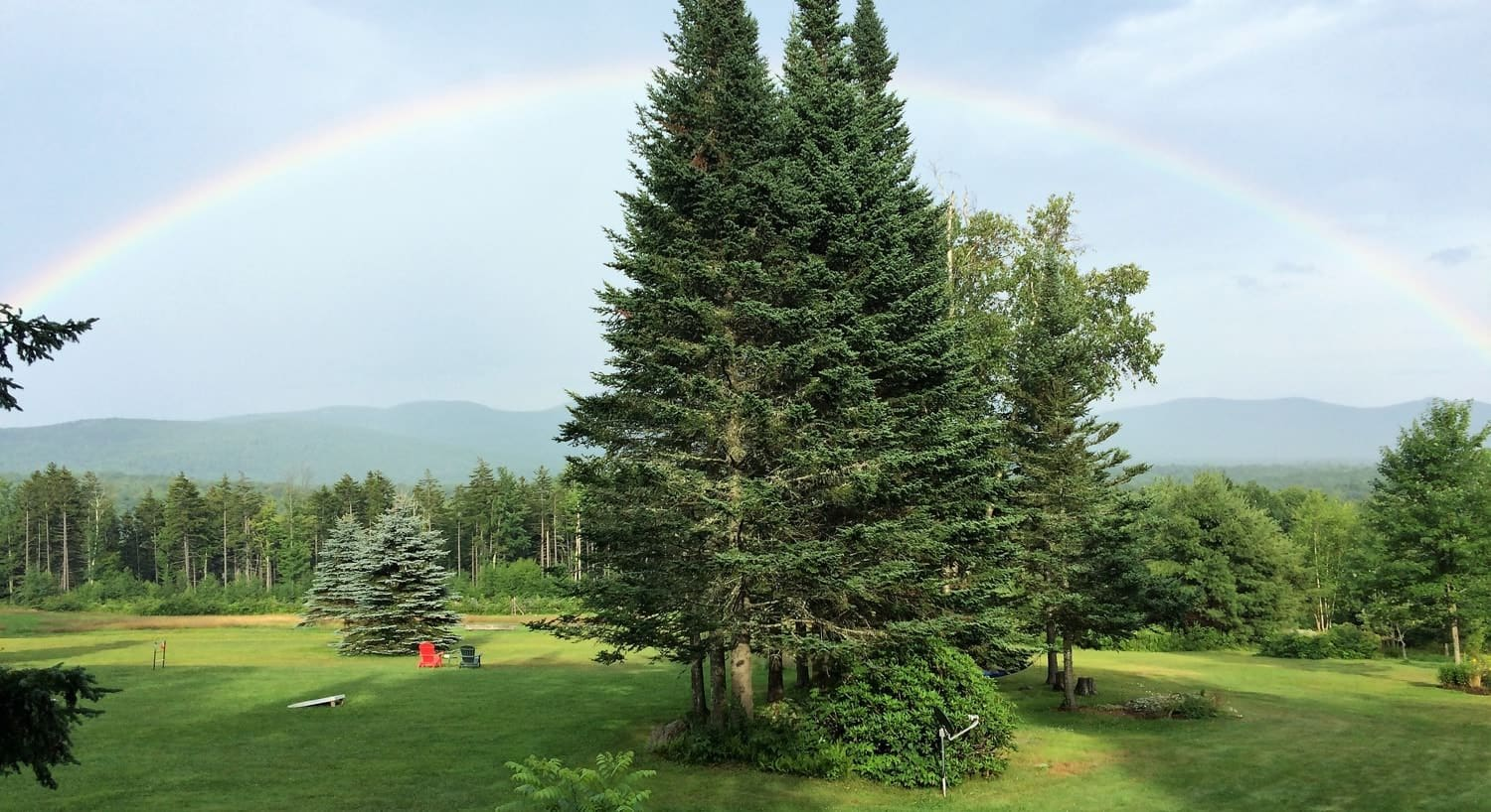 Gorgeous rainbow arced over the properties green grass, trees and distant hills