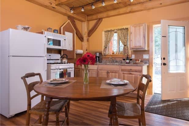 Blackberry Bend kitchen with glass door, window over sink, rustic cabinets, white appliances and round dining table