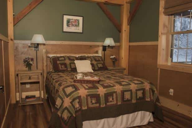 Evening Star guest room with wood floor, window, bed with rustic bedding and two nightstands with lamps