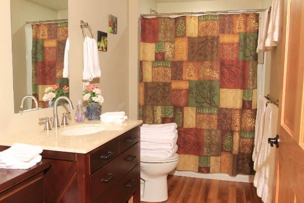 Evening Star guest bath, wood floor, tub/shower, wood vanity with mirror, and white towels