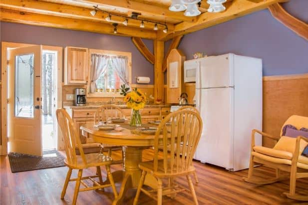 Hemlock Hideaway cabin's kitchen with window, glass door, wood floor and cabinetry, round dining table with chairs