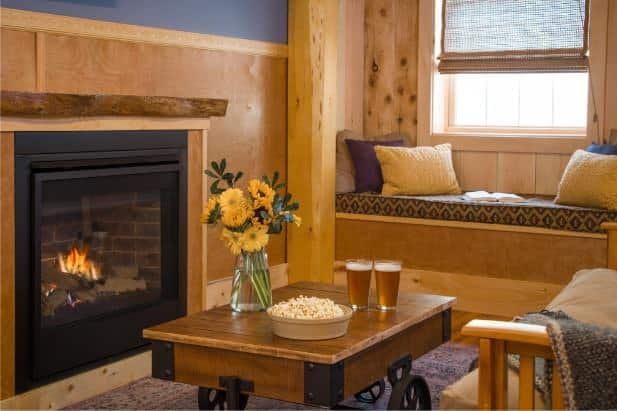Hemlock Hideaway cabin's living area with fireplace, window and window seat, and coffee table topped with popcorn and beer
