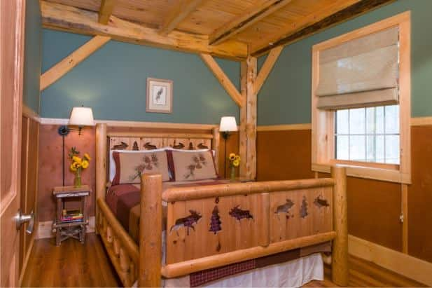 Owl's Branch guest room with rustic wood carved bed, two nightstands with lamps, wood floor and window with shade