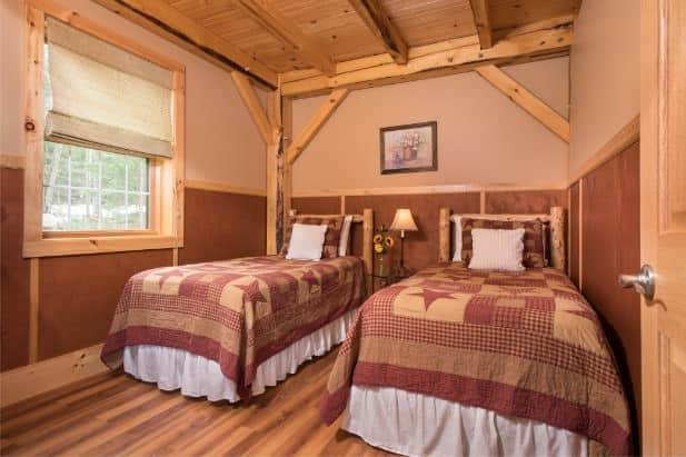Owl's Branch guest room, two rustic beds flanking nightstand with lamp, wood floor and window