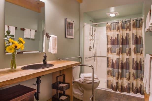 Owl's Branch bathroom with tile floor, tub/shower, rustic vanity open underneath, mirror and white towels