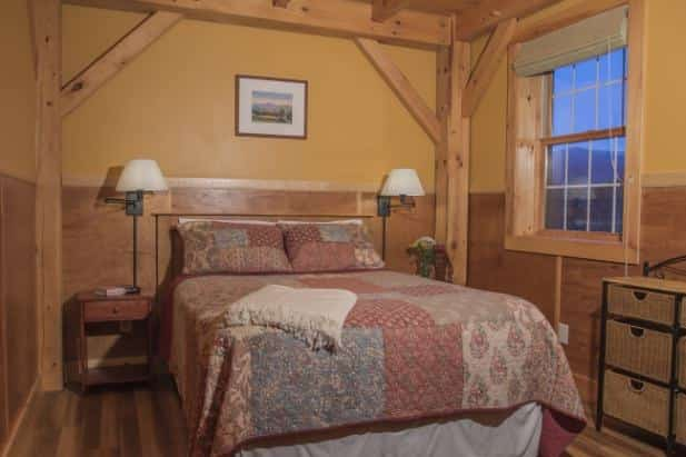 Peak Perspective guest room, quilted bed, two nightstands with lamps, wicker chest of drawers and window with shade