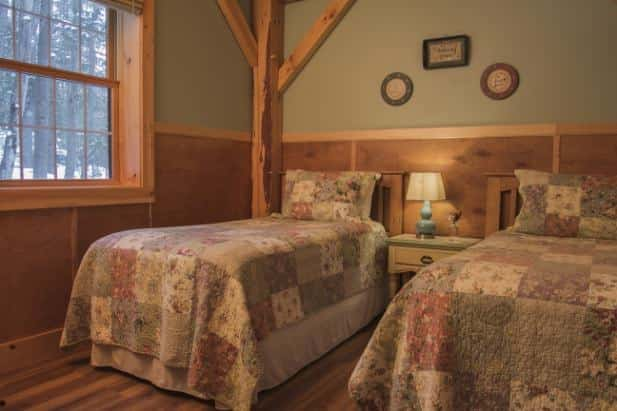 Peak Perspective guest room, two beds with pastel quilt flanking nightstand with lamp, light green walls, wood floor and window