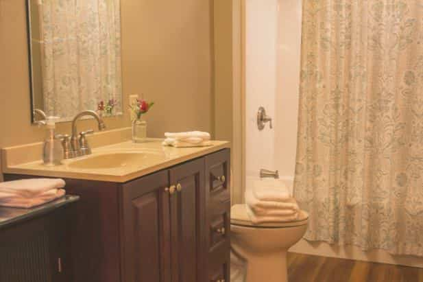 Peak Perspective bath with tub/shower, vanity with sink and mirror, wood floor, and white towels