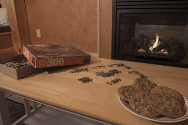 Serene Outlook cabin coffee table topped with fresh baked cookies and a puzzle in front of a warm fire