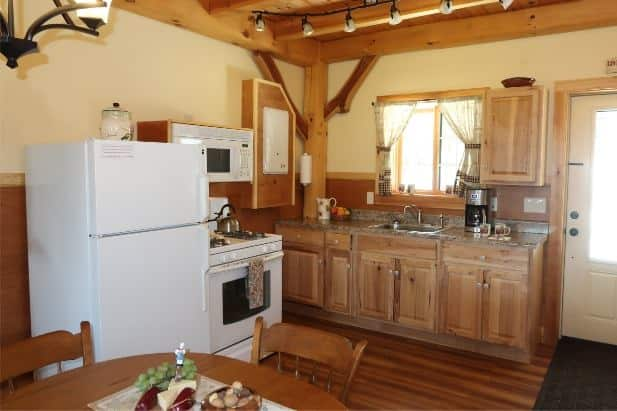 Sunrise Vista Cabin's kitchen with wood floor, ceiling and cabinets, warm beige walls, kitchen sink window and white appliances