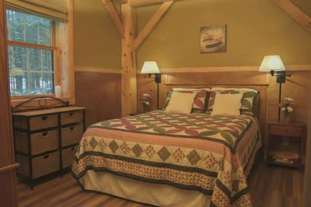 Sunrise Vista guest room, rustic bed with quilt, two nightstand with lamps, and wicker chest of drawers under window