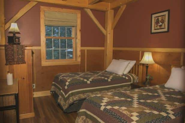 Sunrise Vista guest room, two rustic beds flanking nightstand with lamp, window with shade, and dresser