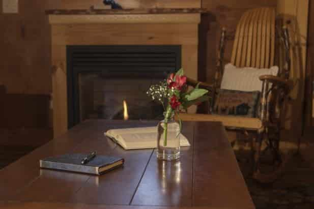 Sunrise Vista coffee table topped with guest book and flowers and a rustic rocking chair and fireplace in the background