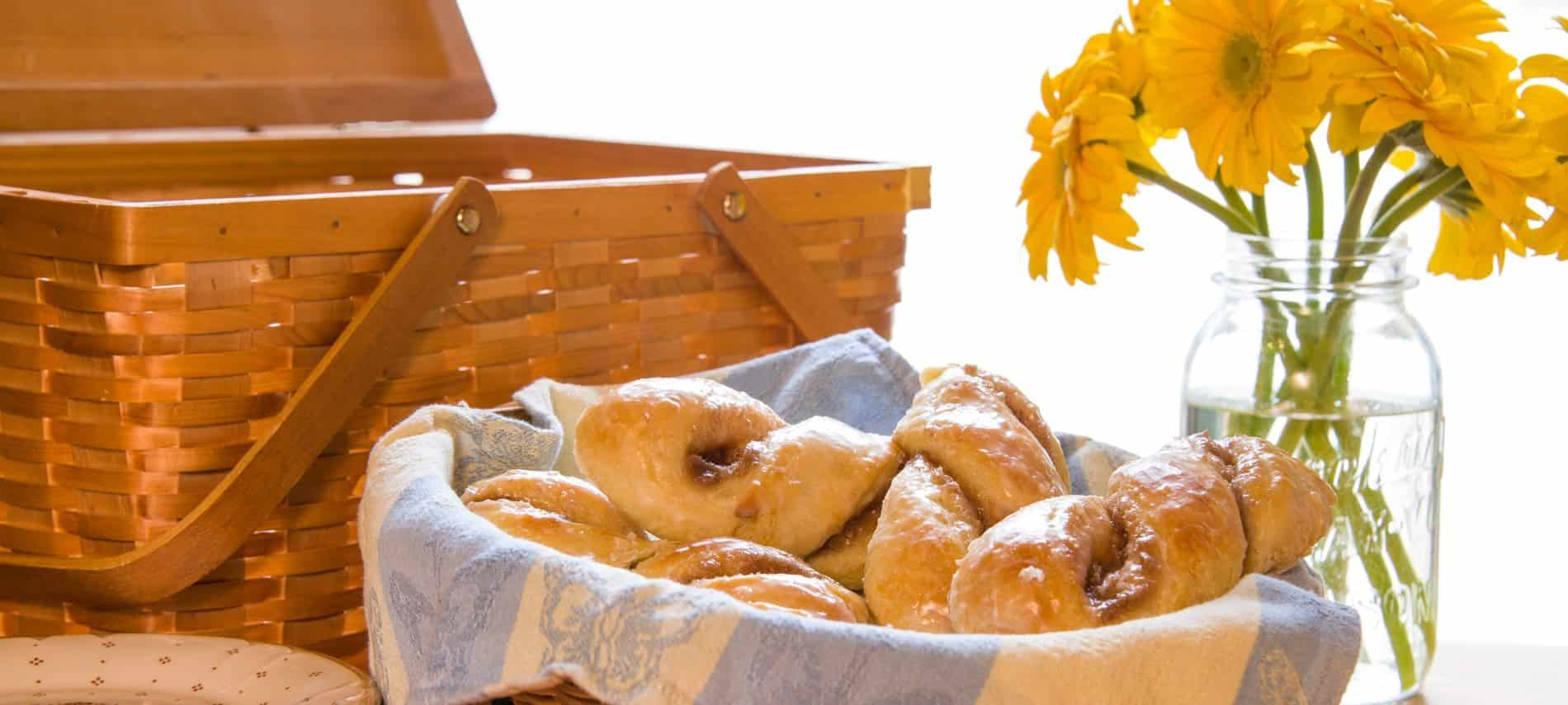 Wooden picnic basket next to a basket of fresh glazed twisted rolls and a glass Mason jar filled with bright yellow flowers