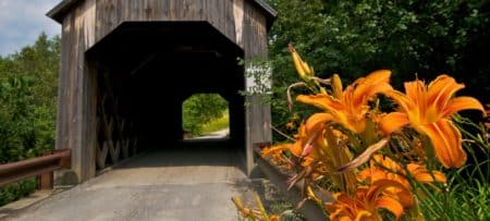 Wooden covered bridge surrounded by lush green trees and bright orange lilies in the foreground
