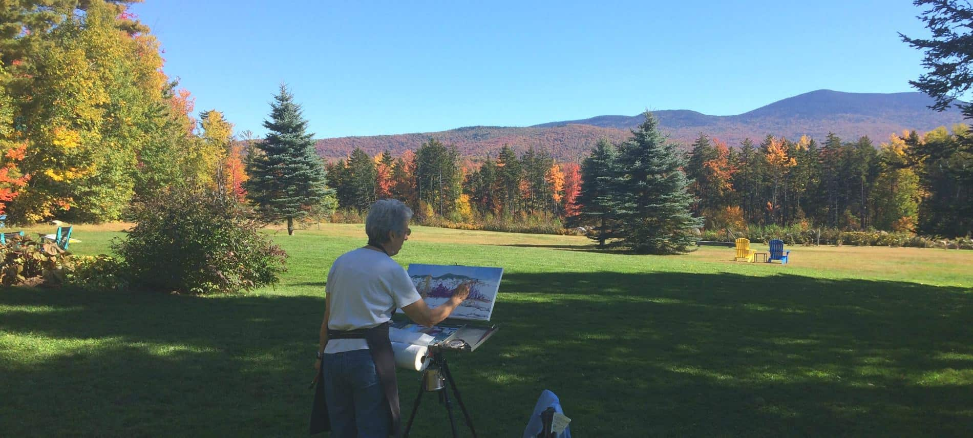Person standing outside in the grass painting the view of green grass, colorful trees in the fall and distant hills