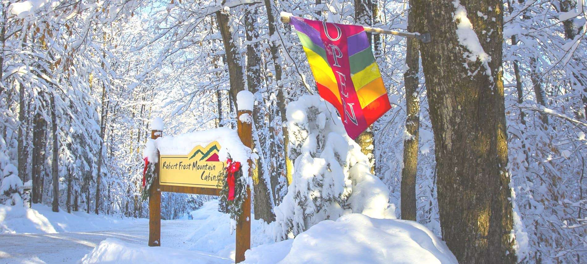 Entrance, wood and yellow sign that reads Robert Frost Mountain Cabins, colorful open flag, all surrounded by white snow covered trees and ground