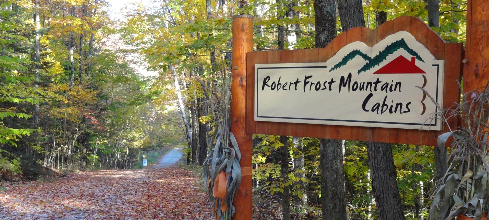 Wooded entrance sign that says, Robert Frost Mountain Cabins, and a road covered with fallen leaves and surrounded by trees