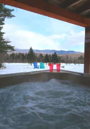 View from a bubbling hot tub of snow-covered ground, pine trees and distant hills