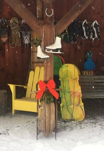 Side of a cabin with hanging pairs of snowshoes, propped up sleds, and a pair of hanging white ice skates