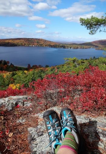 Stunning view of the area from a rocky hilltop in the fall, colorful leaves all around, and distant hills surrounding a large lake