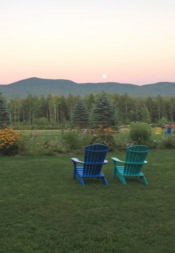Two Adirondack chairs, one blue and one turquoise, on green grass overlooking pine trees, and the sun setting behind distant hills