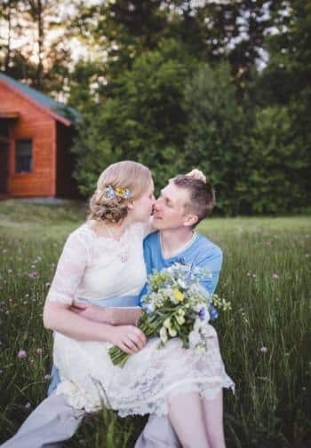 Woman sitting on a man's lap in the grass holding fresh flowers with green trees and a cabin in the background