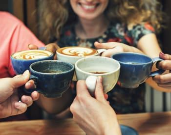 Women sitting a table clinking pottery cups filled with hot cocoa