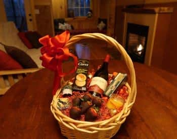 Oval basket with handle filled with wine, crackers, cheese and chocolate covered strawberries